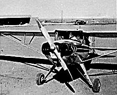 Don Donelan airplane at Saratoga airport in 1950's with hanger to left and Saratoga in background to right